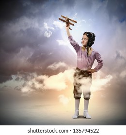 Image of little girl in pilots helmet playing with toy airplane against clouds background