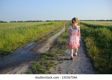 An image of a little girl walking on the road