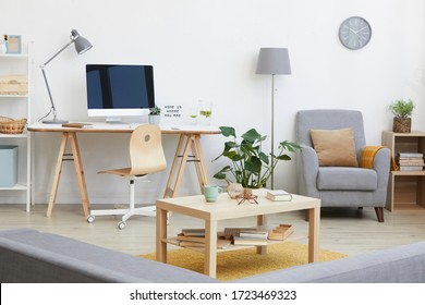 Image of living room with workplace with computer monitor on it and other modern furniture in the house