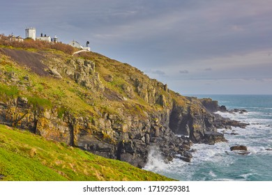 Image of the Lizard Point Lighthouse, with the headland, cliffs, sea and overcast sky. Lizard Point, cornwall, UK