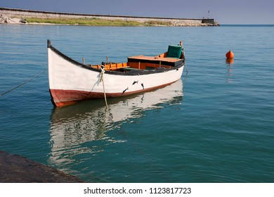 An Image of Lonely Boat. A Skiff Tied to a Dock.