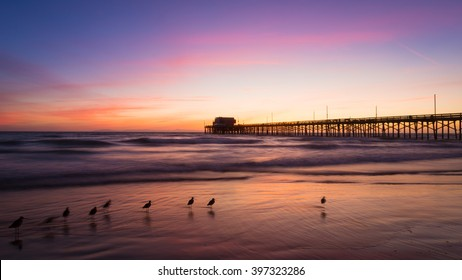 The image is a long-exposure shot of the Newport Beach Pier at sunset in Newport Beach California.