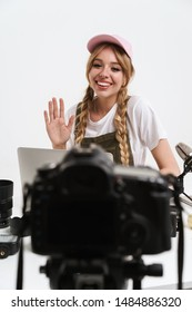 Image of lovely girl recording blog broadcast with microphone about new professional photocamera and technics isolated over white wall in studio