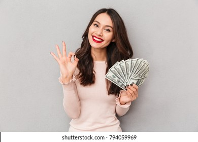 Image of lucky brunette female holding fan of 100 dollar bills being excited to win cash prize showing OK sign, over gray wall