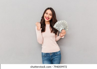Image of lucky brunette female holding fan of 100 dollar bills being excited to win cash prize, expressing victory and wealth over gray wall