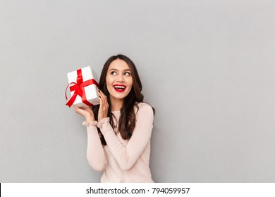 Image of lucky woman holding bithday present with red bow, being happy to win prize being isolated posing over gray background