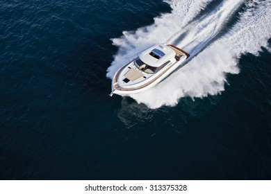 Image of a luxurious yacht cruising through the sea on a sunny day