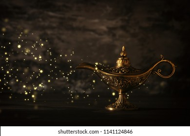 Image of magical mysterious aladdin lamp with glitter sparkle lights over black background. Lamp of wishes