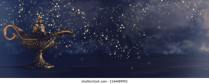 Image of magical mysterious aladdin lamp with glowing glitter lights over black background. Lamp of wishes