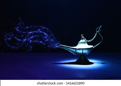 Image of magical mysterious aladdin lamp with glitter smoke. Dark background and dramatic light