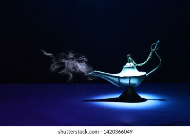 Image of magical mysterious aladdin lamp with smoke. Dark background and dramatic light