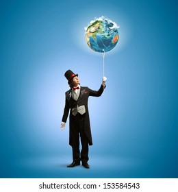 Image of magician in hat holding globe. Ecology concept.