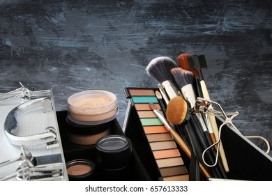 Image of makeup cosmetics beauty tools and brushes in front of black wooden background
