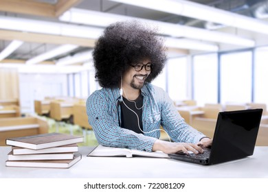 Image of a male college student is studying with a laptop and books on the desk while using an earphone in the classroom