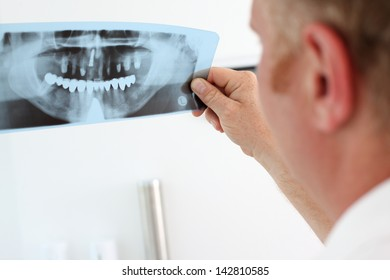 Image of male doctor holding and looking at dental x-ray