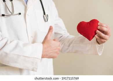 Image of  male doctor showing heart shape and thumb up.
