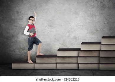 Image of a male elementary school student standing on the books stair. Concept of study hard