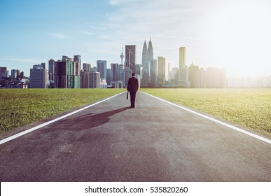 Image of male entrepreneur walking on the road while carrying suitcase