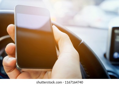 Image of male hand holding a phone whilst inside a car