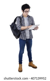 Image of male high school student using a digital tablet computer while standing in the studio, isolated on white background