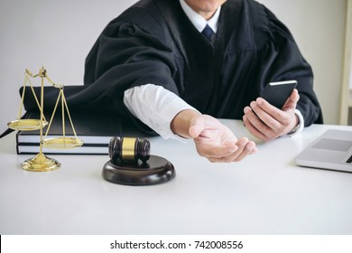 Image of Male lawyer or judge importune bribes client, working with phone and Law books, report the case on table in modern office, Law and justice concept.