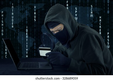 Image of male villain wearing mask and using laptop computer while holding credit card
