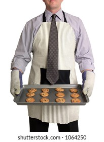 Image of a man against a white background, wearing a kitchen apron and oven mitts over business attire. He is holding a cookie sheet full of chocolate chip cookies in front of him.