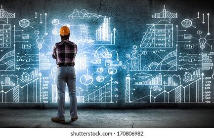 Image of man builder looking at media screen