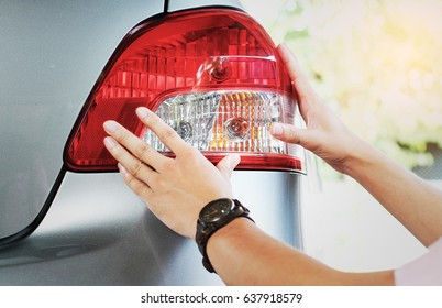 Image of a man checking his tail light before traveling.