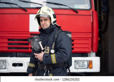 Image of man fireman with mask in hands near fire truck