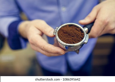 Image of man with ground coffee in hands