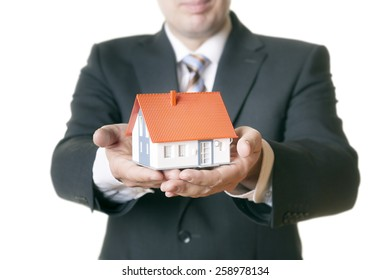 An image of a man holding a house in his hands