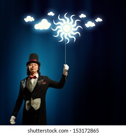 Image of man magician with balloon against color background