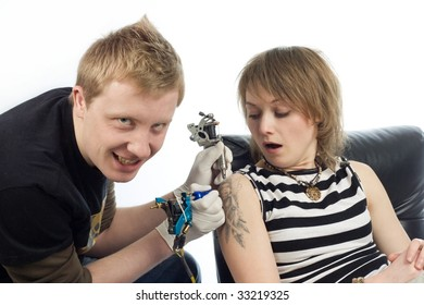 An image of a man making tattoo to a scared woman