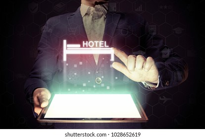 Image of a man with a smartphone in his hands. He presses on the hotel icon. Search and online reservation of hotel.