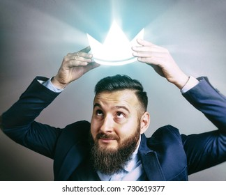 The image of a man in a suit that puts a luminous royal crown on his head. The concept of careerism, achieving the goal, smugness, egoism, success and etc.