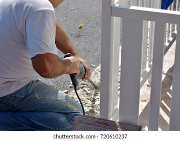 Image of man worker holding ceramic tile drill machine while drilling old tiles to replace with new floor
