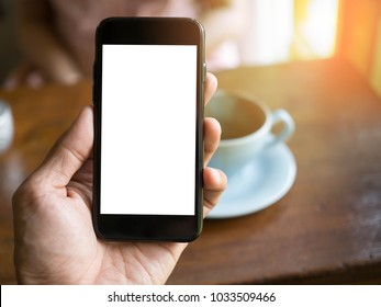 image of man's hand is holding a black cell phone with blank white screen and blur silver laptop on wood table in coffee cafe  background