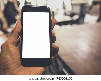 Image of man's hand is holding a black cell phone with blank white screen that you can put any ideas in this space at coffee cafe background