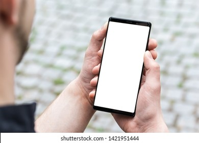 Image of mans hand holding modern black mobile phone with blank white screen. Man using mobile smart phone, close up.