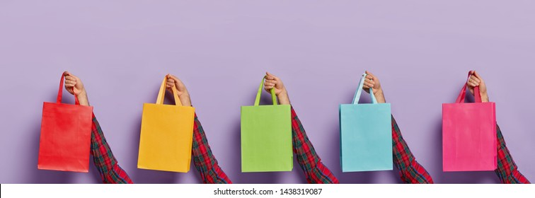 Image of mans hands with various colorful shopping bags isolated on purple background. Black Friday. Consumerism, sale, shopping and purchasing concept. Unknown male customer with many packages
