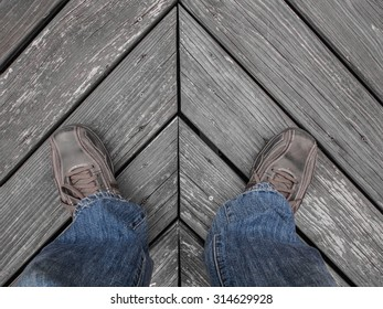 Image of a man's legs and feet wearing blue jeans and brown leather shoes, standing onto of a black and white wooden floor