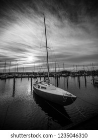 Image of a marina with water reflection and dramatic sky.