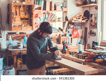 Image of mature carpenter in the workshop, carpenter doing his job in carpentry workshop.