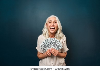 Image of mature happy old woman standing isolated over dark blue background wall looking camera holding money.