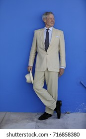 Image of a mature man posing in a suit on blue background