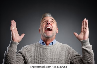 Image of mature man raising his arms up and screaming over grey background