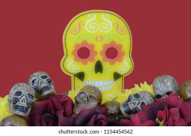 Image for Mexican celebration in October called Day of the Dead. Includes skull party favors laying among artificial red and yellow flowers. Contains background blur of traditional sugar skull mask.