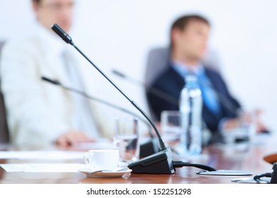 Image of microphone standing on table at conference against defocused background of two businessmen