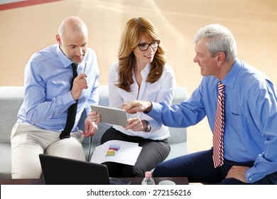 Image of middle age businesswoman holding digital tablet while sitting at office with businessmen and consulting from financial plan. Sales team at work.